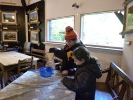 Foto von Schülerinnen beim Mehl mahlen
