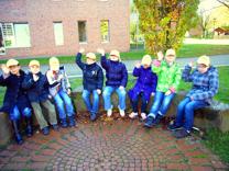 Das Siegerfoto mit den Schülerm der Klasse E-4 in der Sitzecke mit gelben Käppis