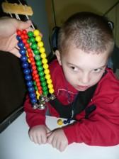 Schüler mit Glöchenkette als Bezugsobjekt zur Hörförderung