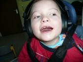 Der Schüler freut sich über sein Hörerlebnis, das ihm über Kopfhörer vermittelt wird