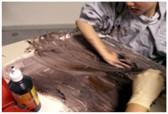 Schülerin bemalt großes Papier mit der Hand mit dunkler Farbe