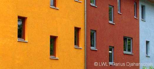 Gelbe, Rote und Blaue Putzfassaden mit Fenstern