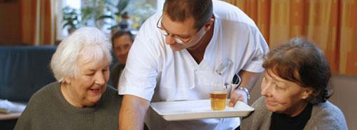 Ein Pfleger versorgt zwei Patientinnen mit Getränken.