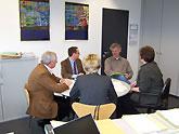 5 Personen sitzen an einem runden Tisch und sprechen miteinander.