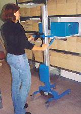 Eine Frau benutzt eine Hebehilfe, um eine Kiste in ein Regal zu stellen.