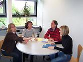 Vier Personen sitzen an einem Tisch in einer Besprechung.