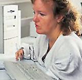 Eine körperbehinderte Frau schreibt auf einer verkleinerten Tastatur.