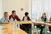 Vier Personen sitzen an einem Tisch in einem Seminar.