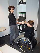 Eine Assistenzkraft reicht einer Rollstuhlfahrerin eine Akte aus dem Schrank.