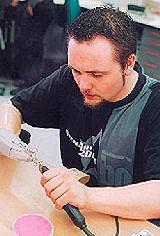 Ein Mann mit einer Handprothese arbeitet in einer Werkstatt.