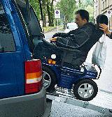 Ein Rollstuhlfahrer fährt über eine Rampe in sein Auto.