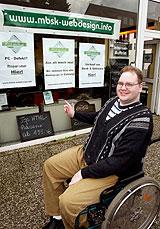 Ein Rollstuhlfahrer vor seinem eigenen Geschäft.