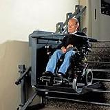 Ein Rollstuhlfahrer gelangt mit einem Treppenlift in die nächste Etage.