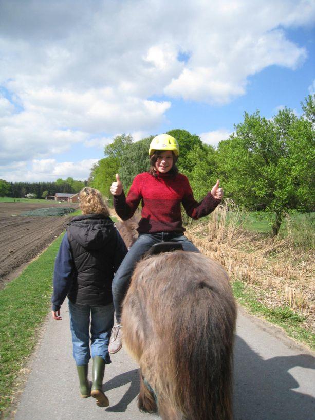 Wir haben mit Frau Dankers einen langen Spaziergang gemacht. Frau Dankers hat ein Seil gehalten mit dem Pferd und Samantha sitzt auf dem Pferd und hat reiten gelernt.