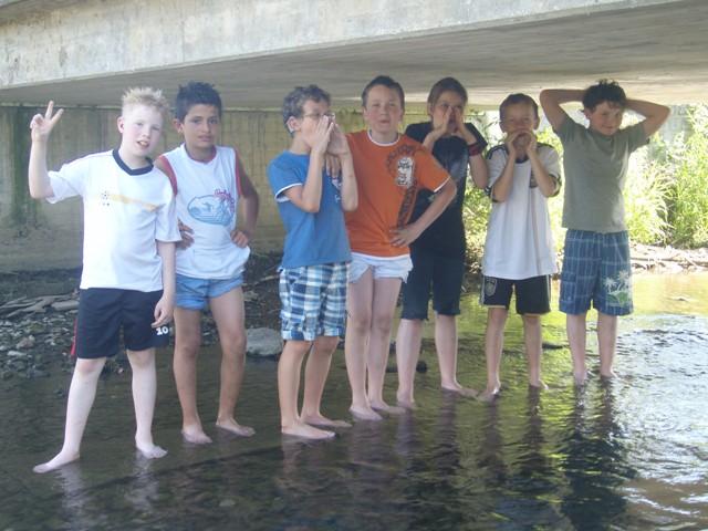 Kinder stehen unter einer Brücke