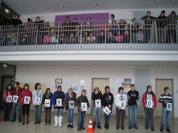 Unten stehen die Schüler mit den Buchstaben bereit – oben die Zuschauer.