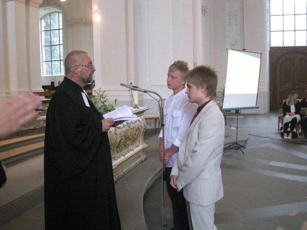 Der Priester bittet die beiden Konfirmanden zu sich nach vorne.