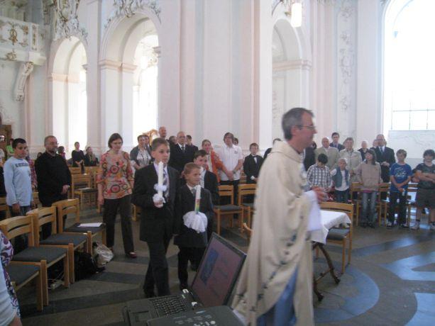 Der Pfarrer und die drei Kommunionskinder ziehen gemeinsam in die Kirche ein,