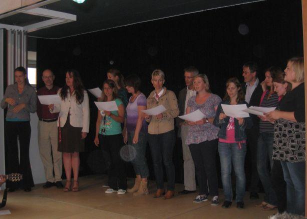 """Der Lehrerchor begrüßt die neuen Schüler mit dem Lied """"Herzlich willkommen!""""."""
