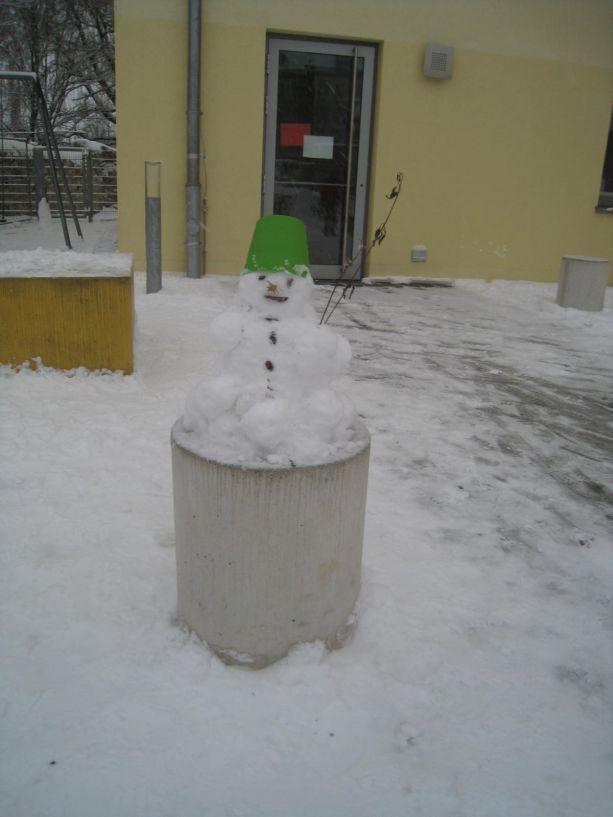 Dieser Schneemann sitzt bequem mit Hut auf einem Stein.