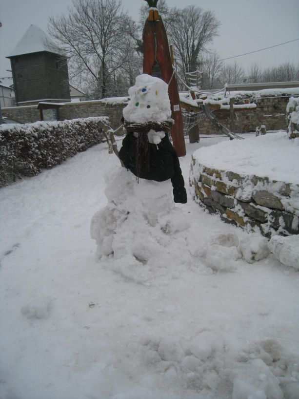 Dieser Schneemann schützt sich mit einem Pullover gegen die Kälte.