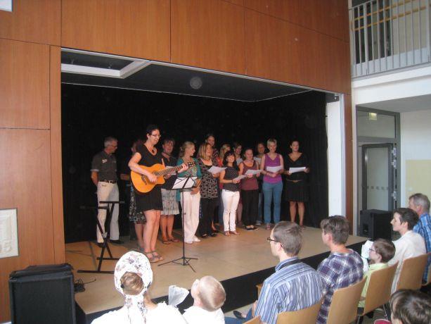 Auf der Bühne in der Aula singt zunächst der Lehrerchor das Begrüßungslied.
