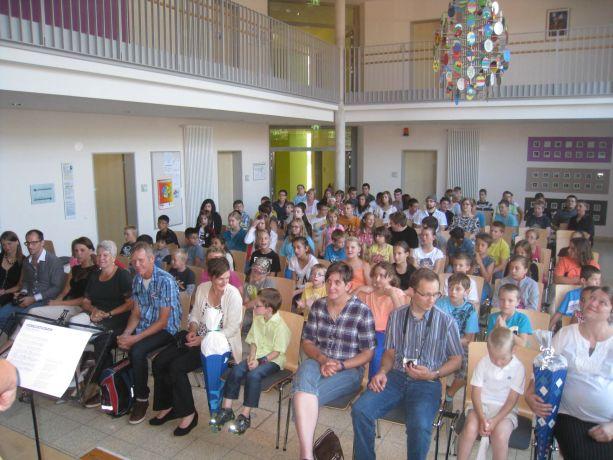 Eltern, Verwandte und Schüler warten gespannt auf das Bühnenprogramm.