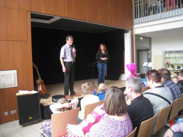 In der Schule begrüßt der Schulleiter Schüler und Eltern zur Einschulungsfeier.