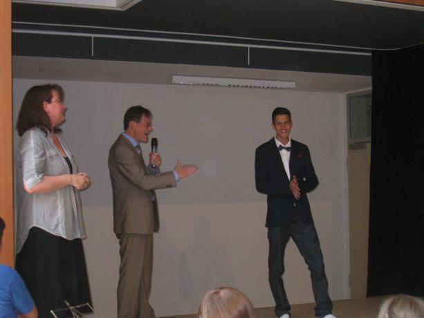 Schließlich übergibt der Moderator das Mikrofon für die Zeugnisübergabe an den Schulleiter.