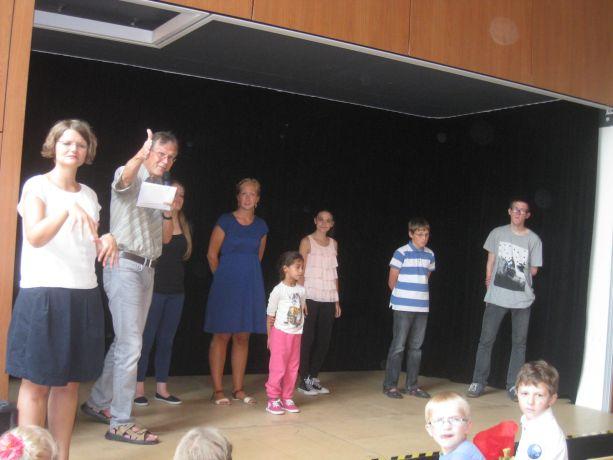 Neue Schüler aus höheren Klassen werden auf die Bühne gebeten.