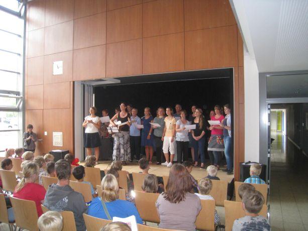 In der Aula der Schule werden die Schüler zunächst vom Lehrerchor begrüßt.
