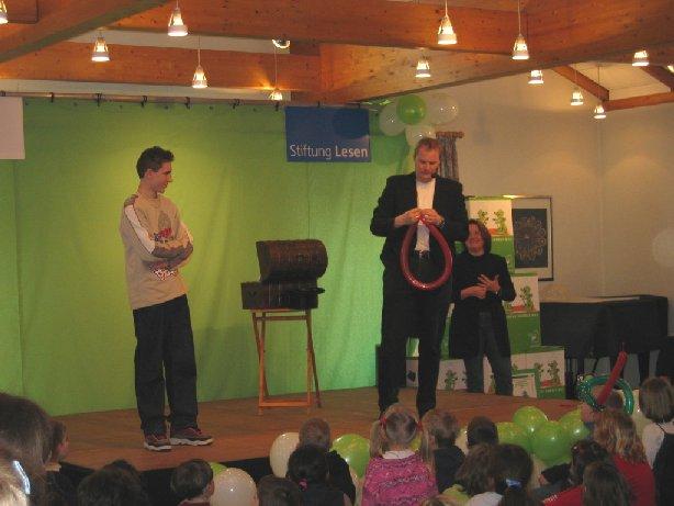 Ein Zauberer betritt die Bühne und zeigt seine Kunststücke mit Schülern.