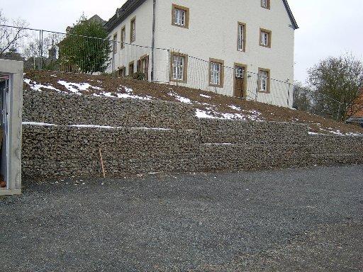 An dieser Seite wird das Grundstück von einer Steinmauer begrenzt.