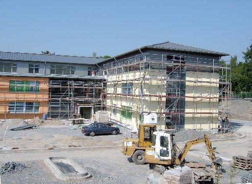 Drei Ansichten zeigen, mit welchen Farben die Schule von außen gestaltet wird.