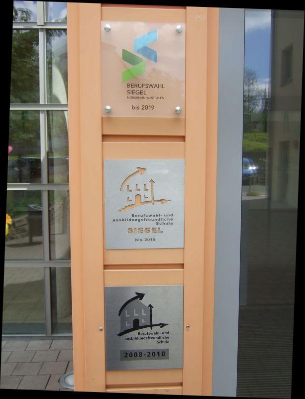 Drei Berufswahl-Siegel schmücken die Eingangstür zur Schule.