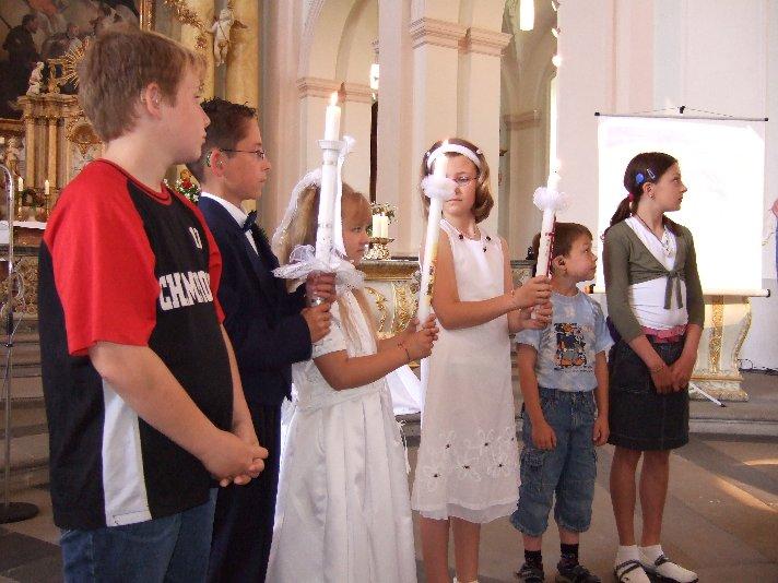 Stolz präsentieren die Kommunionkinder ihre Kerzen.