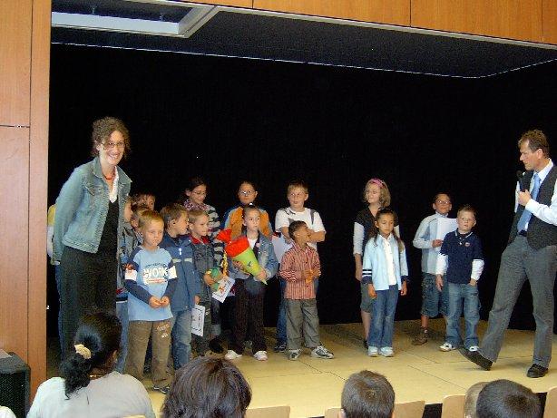Die neuen Schüler stehen mit ihren Paten aus Klasse 4 und ihrer Lehrerin auf der Bühne.