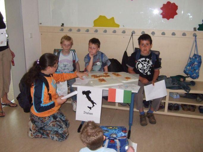 Die Kinder probieren da italienisches Essen.