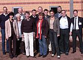 Gruppenfoto vor einer orangefarbenen Backsteinwand