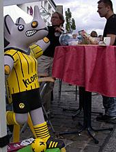 Nashorn-Figur im gelb-schwarzen Trikot vor zwei Personen am Infostand
