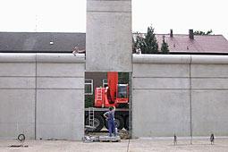 Mauerstück aus Beton schwebt am Kran über einer Lücke in der Mauer