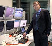 Der Projektleiter vor einer Monitorwand