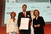 Gerrit Jungk, Leiter der Abteilung Personal und Recht, erhält von Ursula von der Leyen und Dagmar Wöhrl das Zertifikat überreicht.