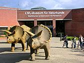 Das Foto zeigt Kinder und zwei Dinosaurier vor dem LWL-Museum für Naturkunde. Foto: LWL-Museum für Naturkunde