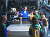 Das Bild zeigt Kinder bei der Besichtigung eines Webstuhls. Foto: LWL-Industriemuseum