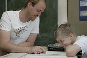 Timo mit Lehrer und Talker im Unterricht