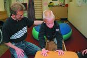 Foto: Körperbehinderter Schüler mit Physiotherapeut