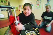 Foto: Körperbehinderter Schüler mit Physiotherapeuten