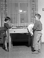 Heimkinder beim Geschirr abtrocknen an einem Kinderwaschtisch