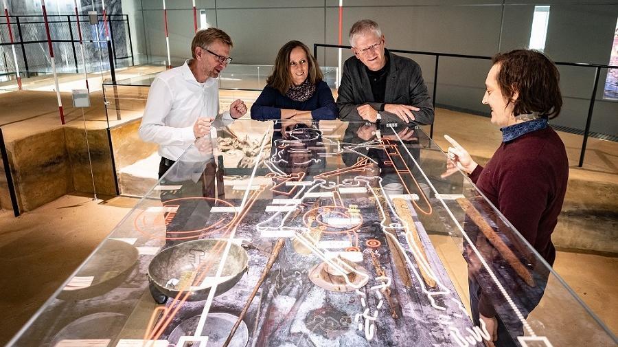 Besucher schauen mit Museumspädagogen auf das Fürstengrab in der Dauerausstellung